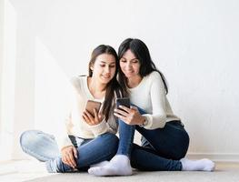 duas lindas amigas enviando mensagens com telefones celulares foto