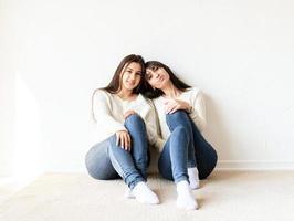 duas melhores amigas sentadas juntas em casa foto