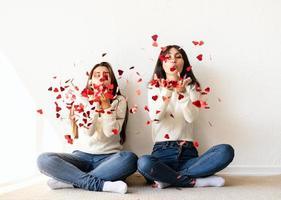 dois melhores amigos se divertindo em casa soprando confete vermelho foto