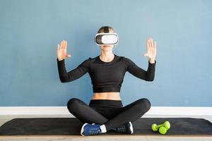 jovem loira com roupas esportivas e óculos de realidade virtual, sentada no tapete de fitness usando o menu interativo de VR foto