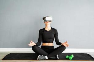 jovem loira com roupas esportivas e óculos de realidade virtual, meditando sobre o tapete de ginástica foto