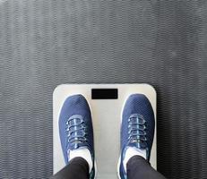 vista de cima dos pés femininos com calçados esportivos azuis, em pé na balança foto