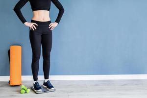 mulher em roupas esportivas pretas em pé na balança foto