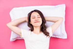 mulher asiática dormindo no fundo rosa foto