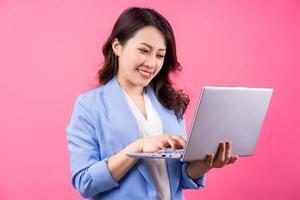 mulher de negócios asiáticos segurando laptop sobre fundo rosa foto