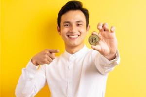 empresário asiático segurando bitcoin na mão com uma cara feliz foto