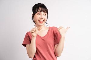 jovem mulher asiática posando em fundo branco, usando o dedo para apontar e mostrar, gesto com a mão foto