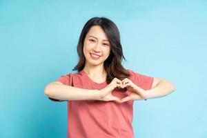 linda mulher asiática moldando o coração com a mão foto