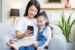 mãe e filha estão assistindo a um vídeo no telefone juntas em casa foto