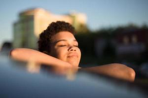 linda mulher afro-americana com cabelo curto perto do carro, estilo de vida foto
