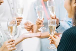 empresários asiáticos do grupo estão fazendo um brinde juntos e conversando em uma festa da empresa foto