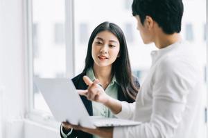 dois colegas asiáticos estão discutindo o trabalho. o empresário está segurando um laptop na mão foto