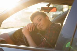 Mulher afro-americana séria e bonita com cabelo curto em um carro, estilo de vida foto