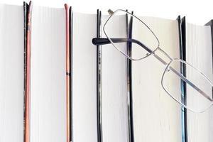 óculos e livros grossos em um fundo branco foto