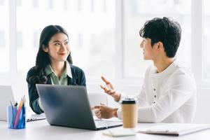 dois jovens empresários asiáticos discutem o projeto de fim de ano foto
