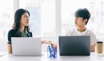 dois jovens empresários asiáticos debatem o projeto de fim de ano foto