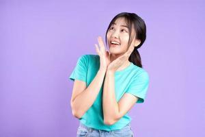 jovem garota asiática em uma camisa ciano em fundo roxo foto