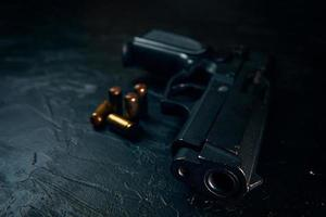 arma preta e balas na mesa. foto