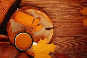 vista superior da composição de outono com uma xícara, uma abóbora, uma torta e um suéter. foto