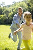 pai perseguindo sua filha enquanto brincava no parque foto