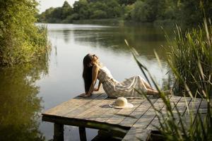 jovem relaxante no cais de madeira no lago foto