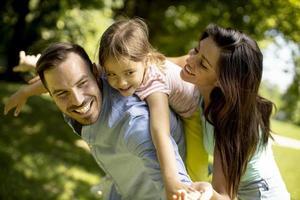 família jovem e feliz com a filhinha se divertindo no parque em um dia ensolarado foto