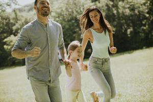 família jovem e feliz com a filhinha correndo no parque em um dia ensolarado foto
