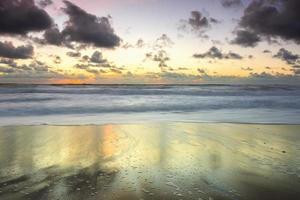 pôr do sol calmo na praia após uma tempestade foto