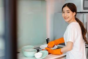 a mulher asiática está lavando a louça foto