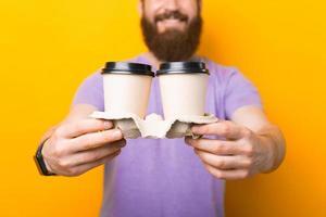 Feche a foto de um homem barbudo sorridente segurando dois copos de café de papel para levar