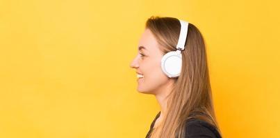 vista lateral retrato de uma mulher sorridente usando fones de ouvido sem fio brancos sobre fundo amarelo foto