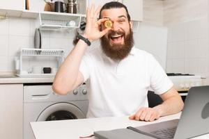 foto de um homem barbudo surpreso sentado em frente ao laptop na cozinha e mostrando bitcoin