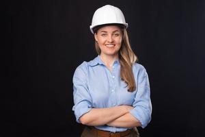 foto de uma jovem arquiteta sorridente usando capacete branco sobre fundo escuro
