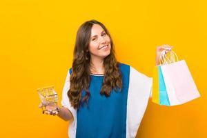 jovem encantadora em pé sobre um fundo amarelo, segurando sacolas e carrinho de compras foto