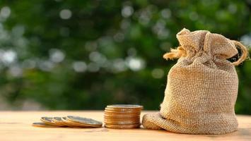 pilha de moedas no fundo da mesa e economizando dinheiro e conceito de crescimento de negócios, finanças e investimento foto