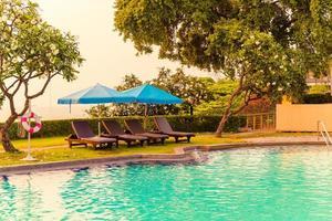 cadeiras de praia ou camas de piscina com guarda-sóis ao redor da piscina na hora do pôr do sol foto