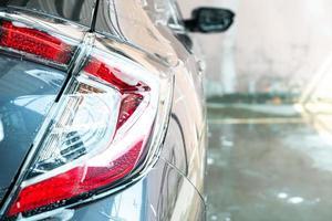 lâmpada de farol de carro de close-up com espuma de lavagem de carro foto