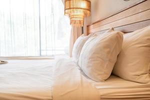 decoração de travesseiro branco na cama no interior do quarto foto