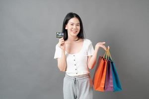 jovem mulher asiática segurando uma sacola de compras e um cartão de crédito em fundo cinza foto
