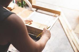 os marceneiros usam lâminas de serra para cortar pedaços de madeira para montar e construir mesas de madeira para seus clientes foto