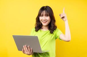 jovem mulher asiática usando laptop em fundo amarelo foto