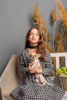 retrato de uma jovem, com seu chihuahua. uma garota em um vestido e um cachorrinho branco. foto