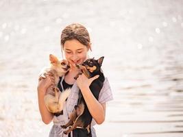 menina com dois chihuahuas nos braços no verão. linda garota adolescente sorrindo em um dia ensolarado. menina animal de estimação foto
