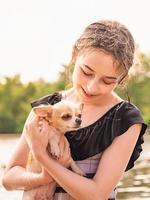 retrato de uma jovem, com seu chihuahua. cachorrinho fofo. menina e um cachorrinho. garota perto do rio foto
