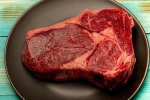 processo de cozimento de bife. a carne está em um prato preto. um pedaço de carne crua em um prato. foto