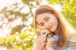 uma garota com um cachorro pequeno em um dia ensolarado de verão. retrato de uma adolescente feliz com cachorro chihuahua. foto