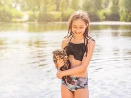 uma garota com um cachorro pequeno em um dia ensolarado de verão. adolescente feliz com cachorro chihuahua. rio verão foto
