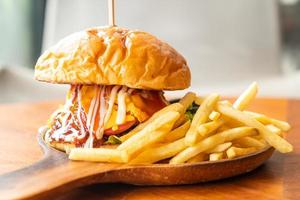 hambúrguer de carne com queijo e molho em prato de madeira foto