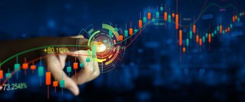 dupla exposição da mão do empresário no indicador financeiro digital do mercado de ações com o fundo da cidade à noite foto