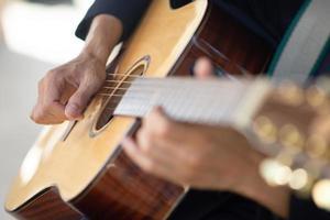 Feche a mão tocando violão e pegue acordes de guitarra foto
